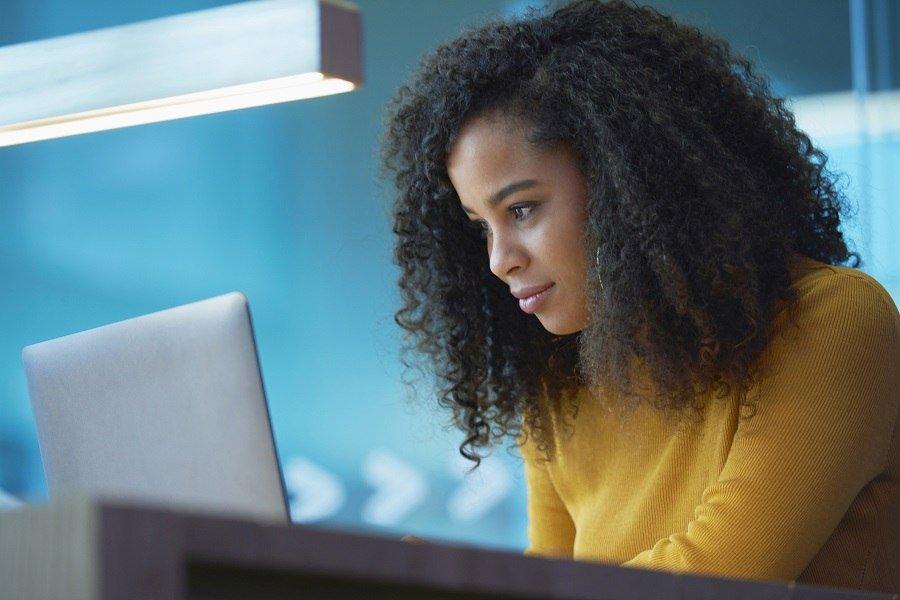 Mulher de pele negra utilizando uma camisa amarela enquanto escreve conteúdo para realizar marketing para marketplace