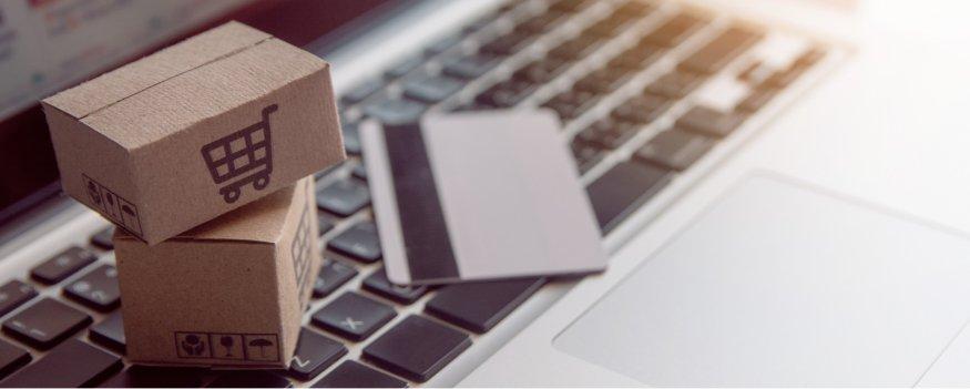 Miniaturas de caixa de papelão em cima de um teclado de computador da cor cinza para simbolizar compras digitais