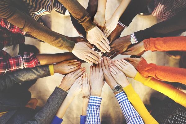 Time de mãos juntas logo depois de concluir o processo de como criar uma startup