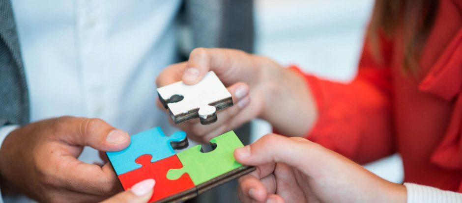 Pessoas juntando as peças de um quebra cabeça como parte do processo de como montar uma startup