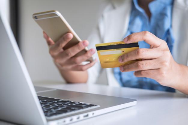 Homem segurando um cartão de crédito para realizar uma compra em marketplace